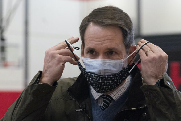 Congressman Jim Himes, D-Conn., adjusts his two masks