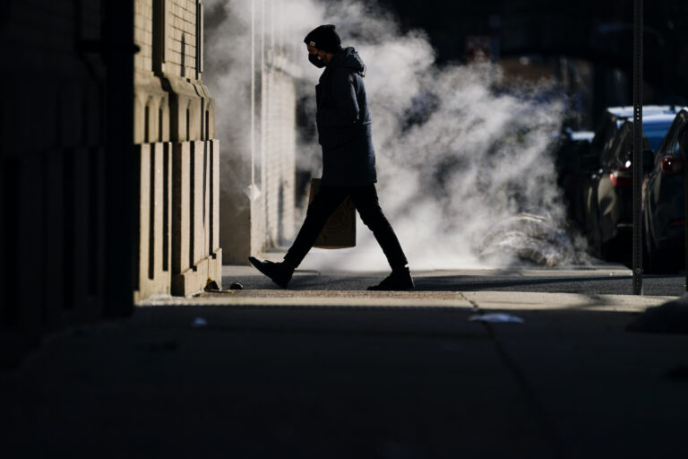 A person wearing a face mask as a precaution against the coronavirus walks in Philadelphia