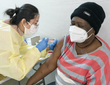Registered Nurse Shyun Lin, left, gives Alda Maxis, 70, the first dose of the COVID-19 vaccine at a pop-up vaccination site