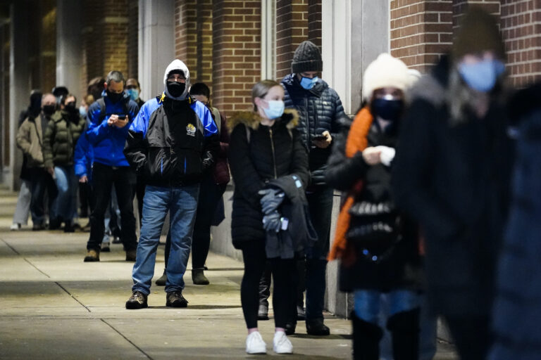 People wait in line at a COVID-19 vaccination site at the Pennsylvania Convention Center
