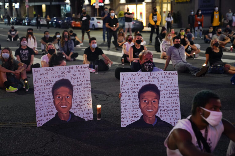 In this Aug. 24, 2020, file photo, two people hold posters showing images depicting Elijah McClain during a candlelight vigil for McClain outside the Laugh Factory in Los Angeles. (AP Photo/Jae C. Hong, File)