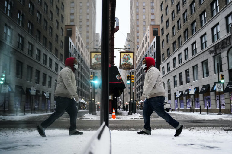 A person, reflected in a window while wearing a face mask as a precaution against the coronavirus, walks during a winter storm in Philadelphia