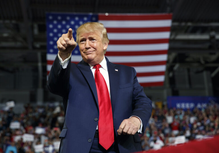 President Donald Trump gestures to the crowd as he arrives to speak at a campaign rally