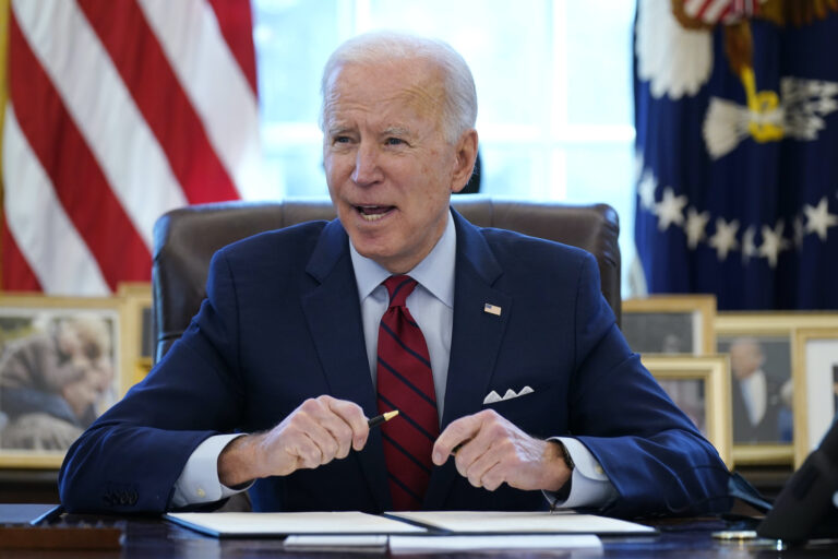 President Joe Biden signs a series of executive orders in the Oval Office
