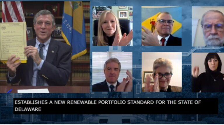 Delaware Gov. John Carney holds a signed copy of legislation mandating an increase in the amount of energy Delaware gets from renewable sources. (State of Delaware screenshot)