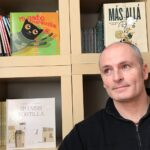Enrique Morás stands in front of a bookshelf