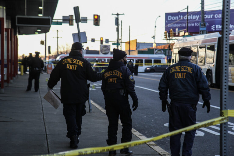 Members of the Philadelphia Police Department's Crime Scene Unit are pictured behind crime scene tape