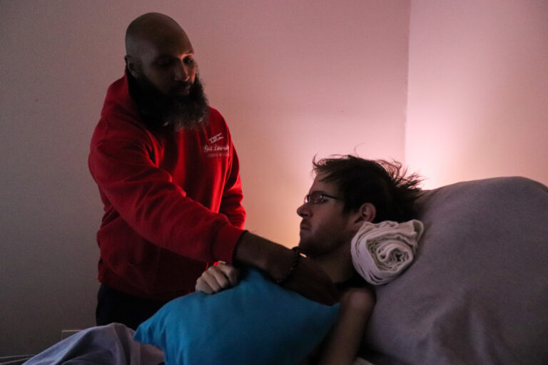 Ray Wall, a licensed practical nurse, positions Steven Sebastianelli in his bed. Wall visits Sebastianelli's apartment every day to assist him in daily living activities. (Madison Karas/WHYY)
