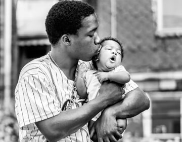 A photograph by Ken McFarlane showing a Black father kissing their baby in Movers & Makers: Made with Love