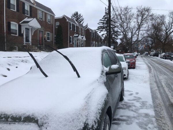 A car with its windshield wipers up amid a snow-covered street in Wilmington