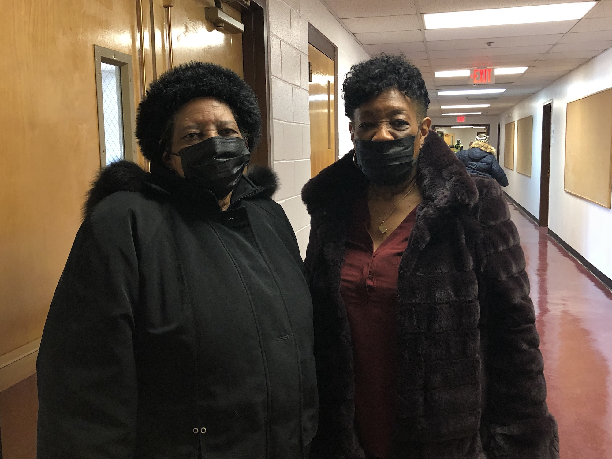 Linda Scott and Mary Lawton, both wearing face masks, stand in a hallfway