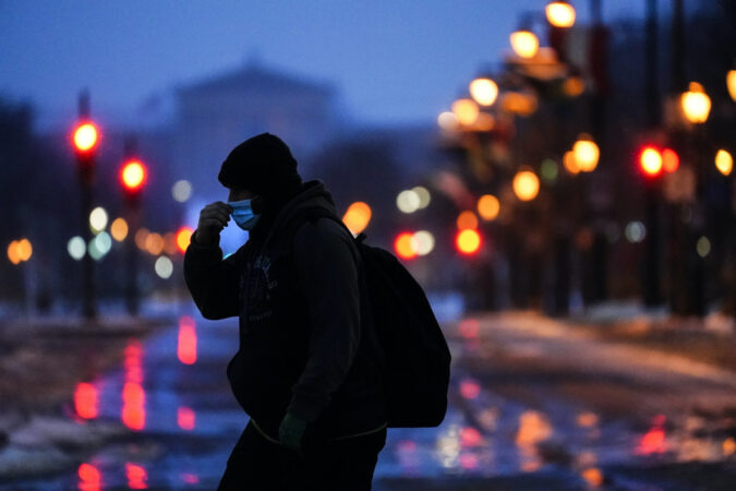 A person wearing a face mask as a precaution against the coronavirus walks during a winter storm in Philadelphia