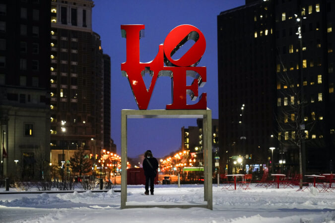 A person wearing a face mask as a precaution against the coronavirus walks during a winter storm near the Robert Indiana sculpture