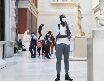 Visitors wear masks at the Metropolitan Museum of Art in October. The museum's director says the Met is considering selling art to pay for operating expenses. (John Minchillo/AP)