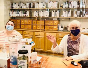 Two women, wearing face masks, sit behind a desk at Avon Grove Library.