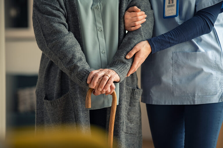 Close up hands of caregiver doctor helping old woman at clinic.