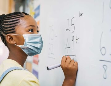 Black schoolgirl solving addition sum on white board during Covid-19 pandemic