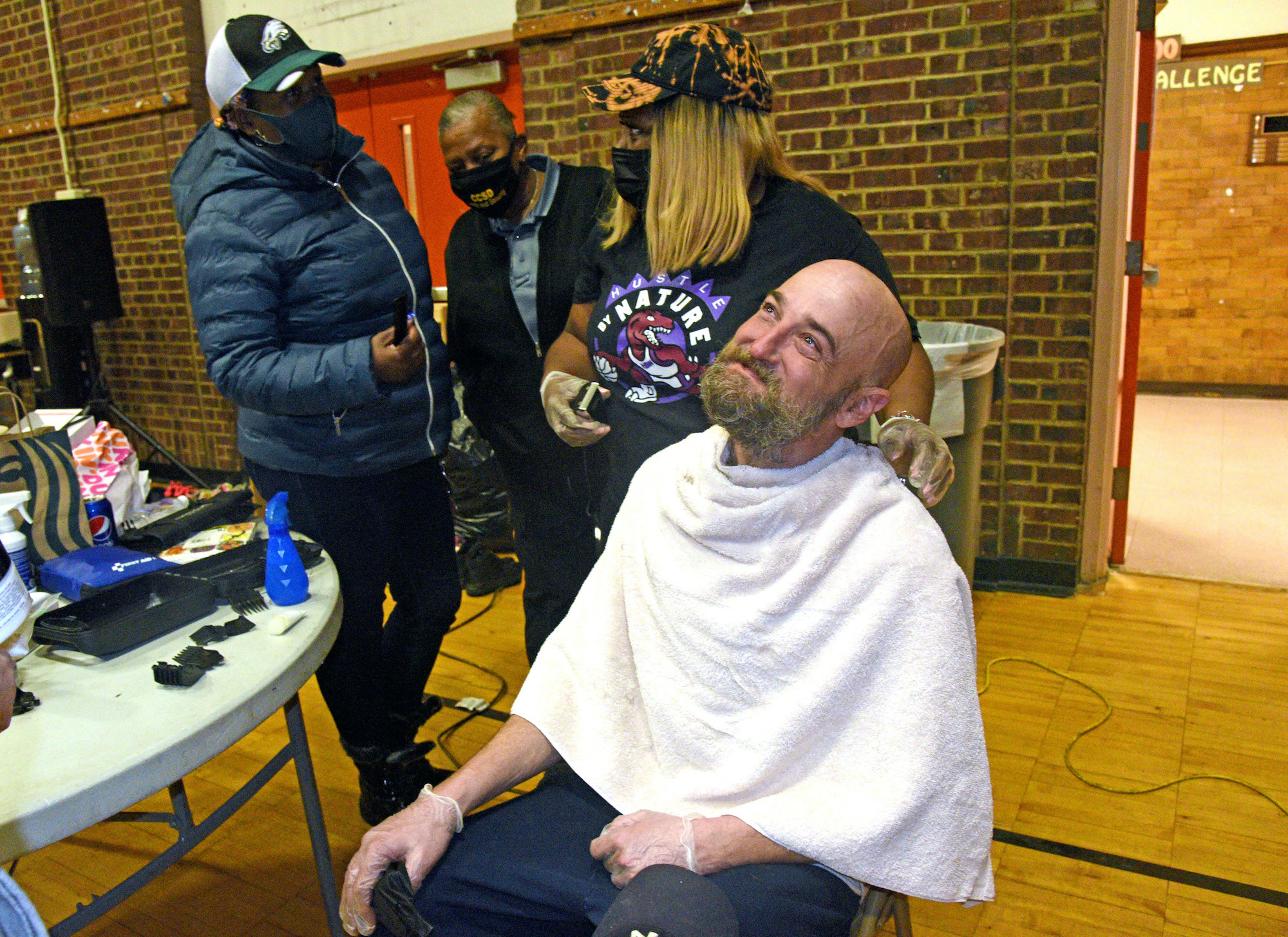 Tawanda Jones gives a patron a haircut.