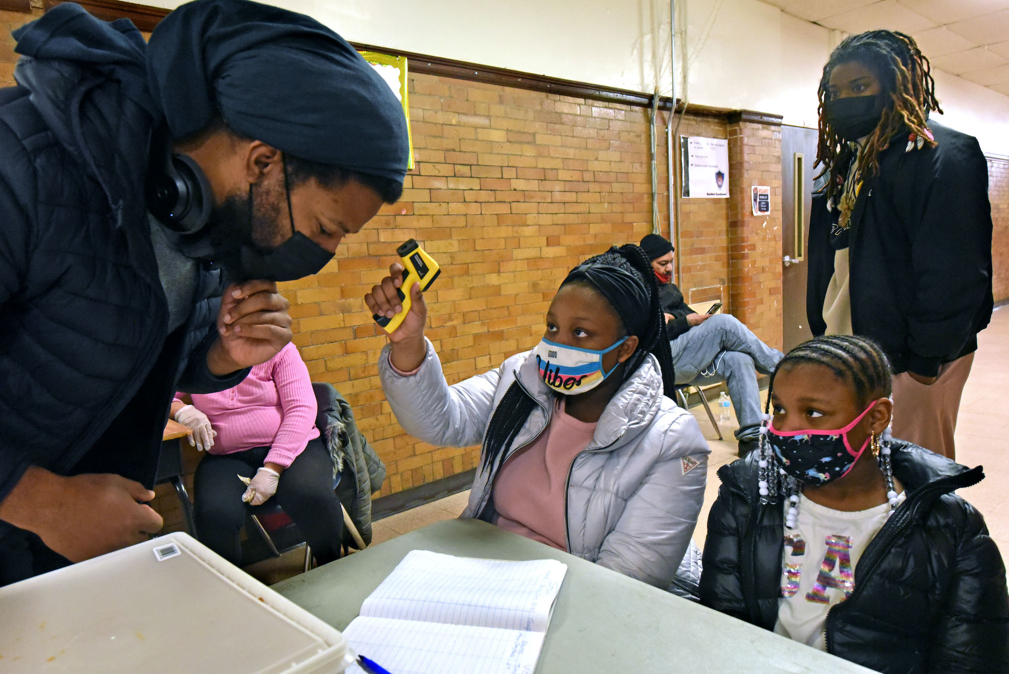 Shaniah Allen, 11, and her sister Taliah Allen, 8; take the temperatures of those who enter