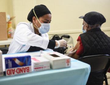 A person administers a COVID-19 vaccine