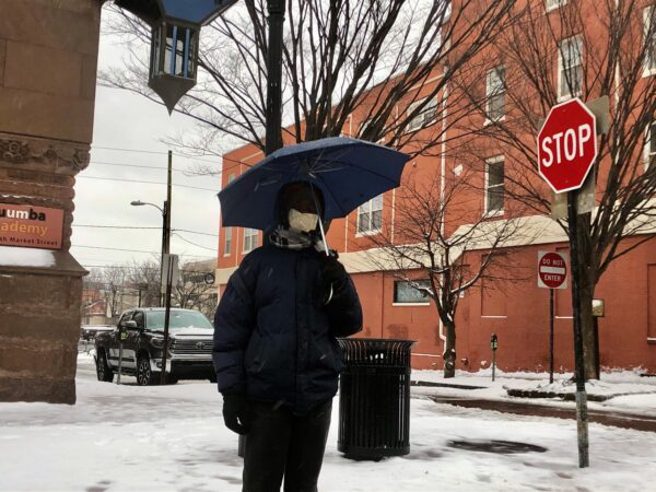 Kyheem Douglas keeps dry from the snow with an umbrella in Wilmington