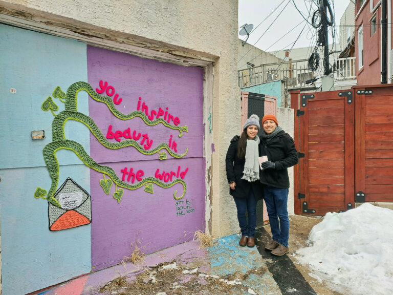 Danielle Brief and Jonah Adams stand next to a mural in South Philly