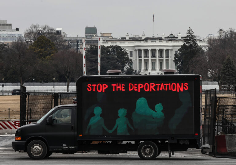 An L.E.D. truck displaying messages expressing concern over the continuing mass deportations of Black immigrants drives past the White House