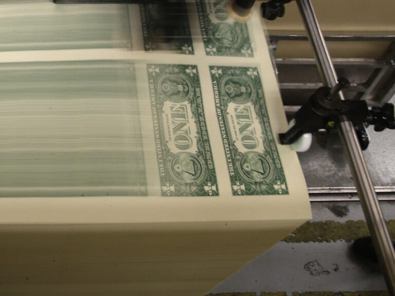 Sheets of one-dollar bills run through the printing press at the Bureau of Engraving and Printing in 2015 in Washington, D.C. Congressional forecasters projected the federal deficit this fiscal year will hit its highest since World War II. (Mark Wilson/Getty Images)