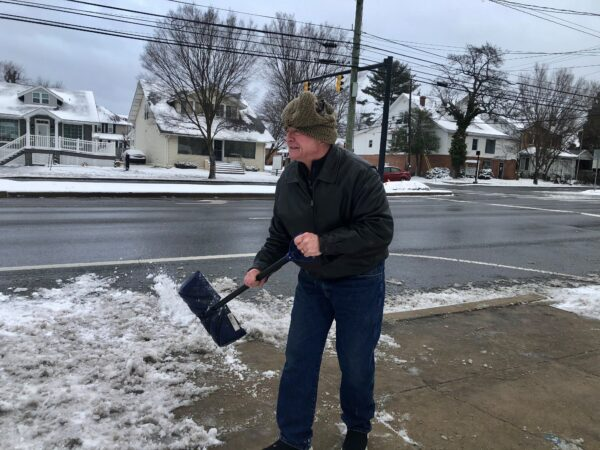 Joe Janvier shovels the sidewalk in in front of his jewelry store in Elsmere