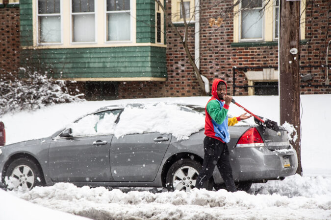 A Philadelphian clears off their car in Philadelphia's Frankfort neighborhood.