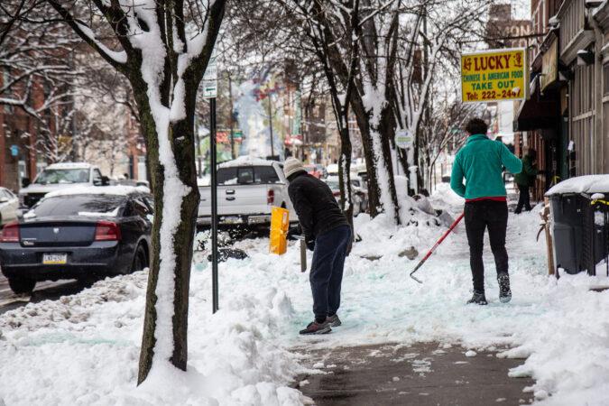 Residents clear the sidewalk in Belmont