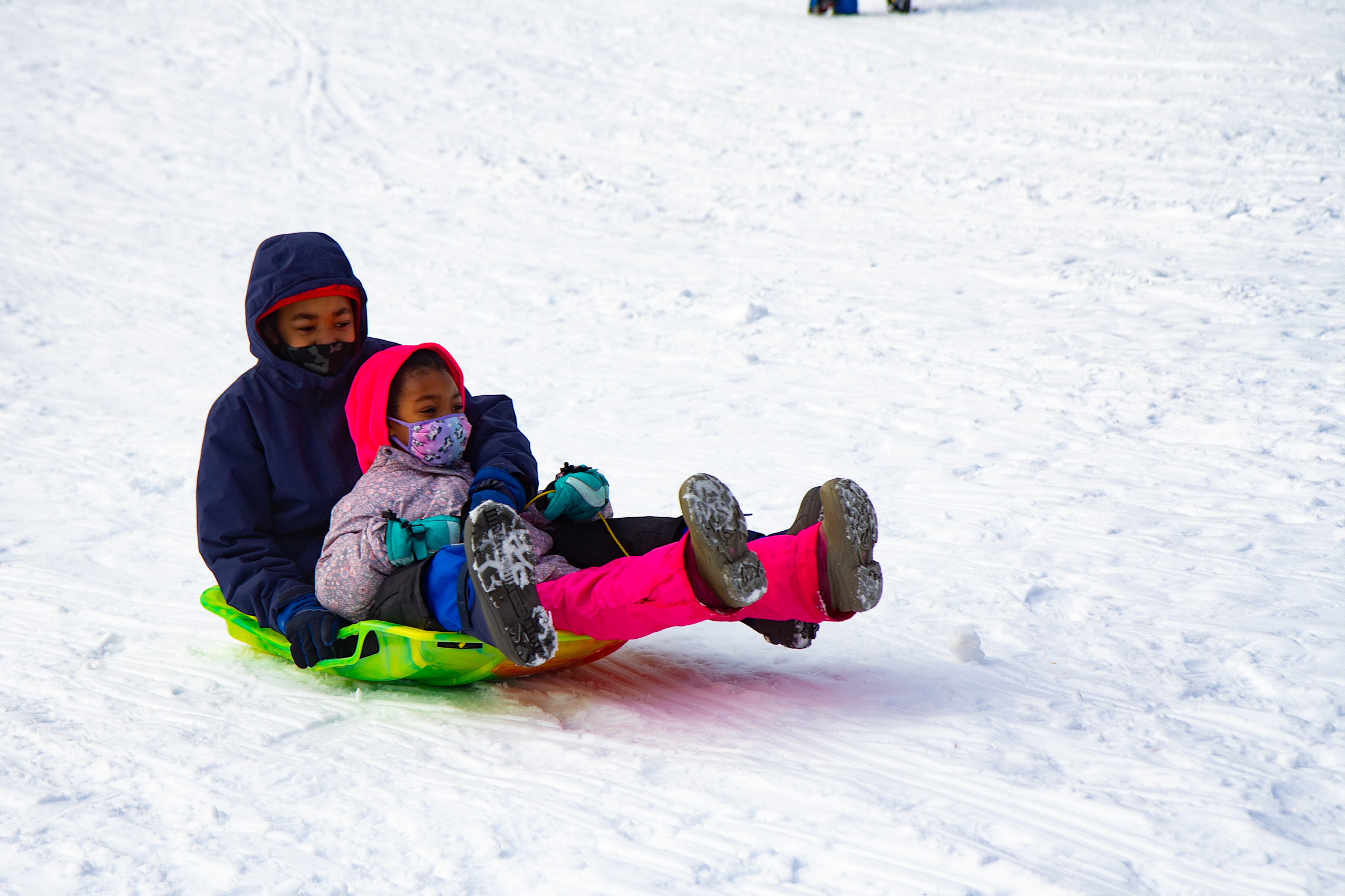 Two happy sledders skid down the dome at Clark Park in West Philadelphia.