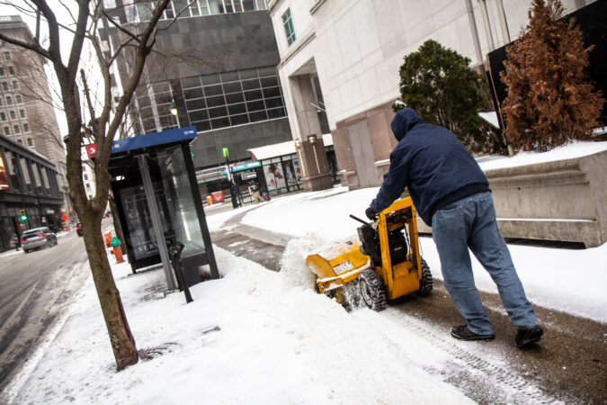 A person clears the sidewalk of snow in Center City