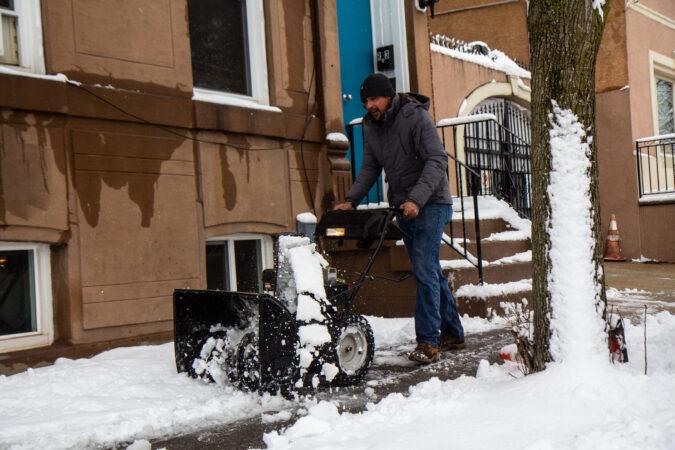 A snowblower clears sidewalks in Philadelphia's Kensington neighborhood