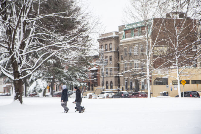 Residents walk in the snow at Norris Square Park in Kensington