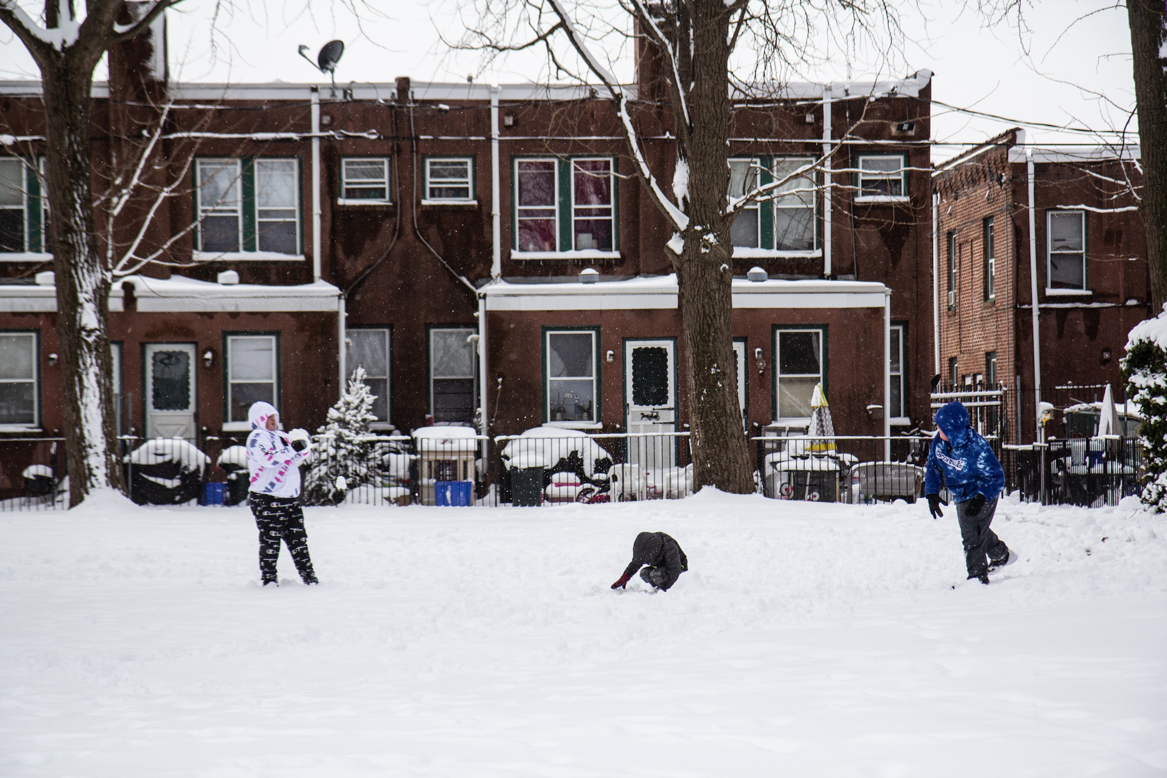 Kids toss snowballs around a courtyard in Philadelphia.
