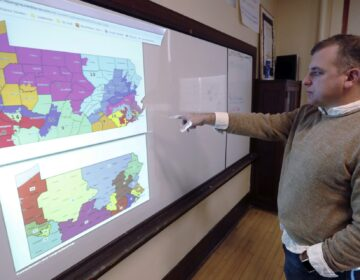 William Marx, points to projected images of the old congressional districts of Pennsylvania on top, and the new re-drawn districts on the bottom, while standing in the classroom where he teaches civics in Pittsburgh on Friday, Nov. 16, 2018. (Keith Srakocic/AP Photo)