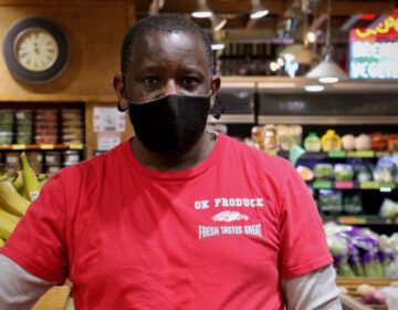 Sam Gatuka is the owner of OK Produce in the Reading Terminal Market. (Emma Lee/WHYY)