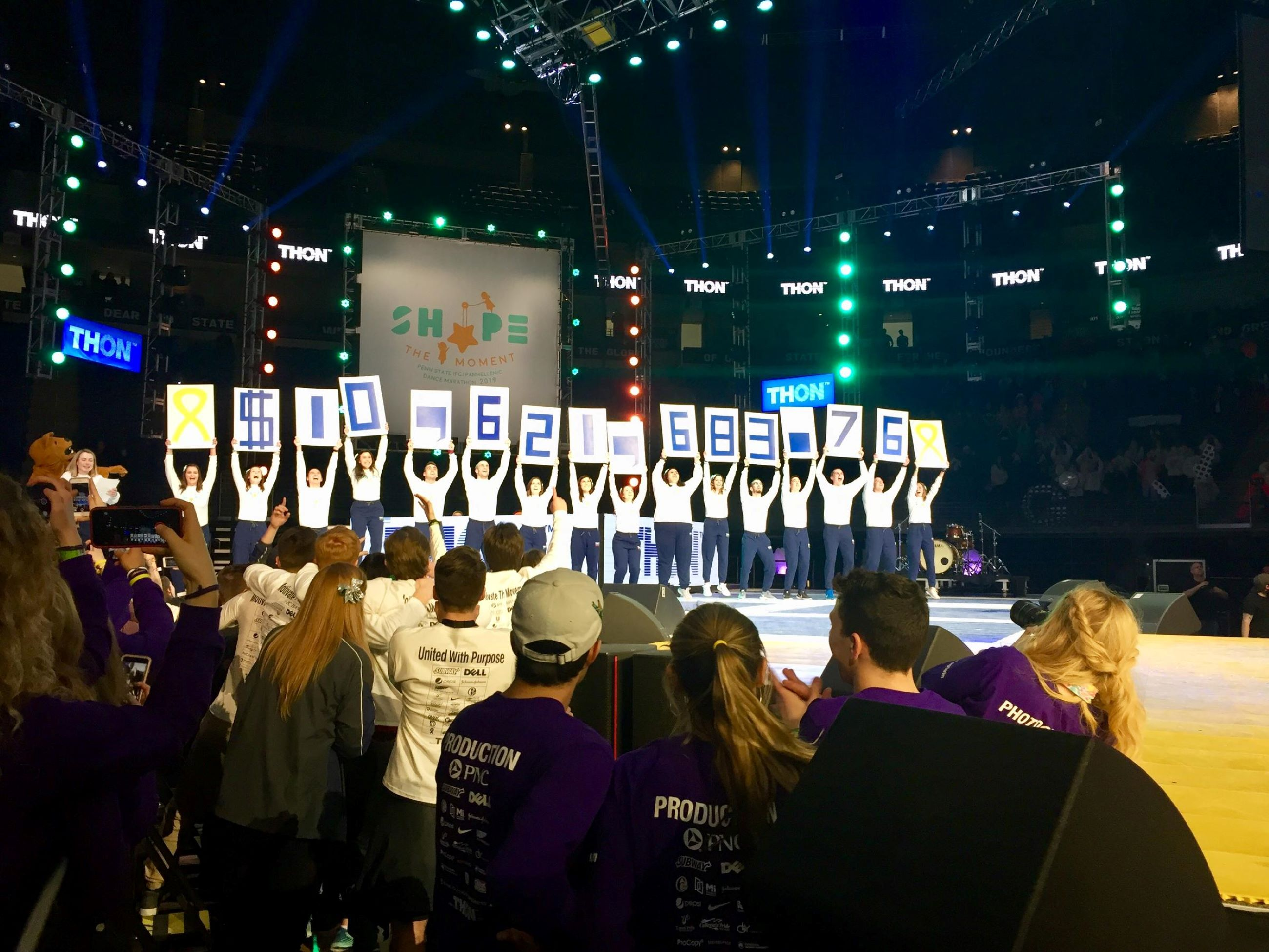 Penn State THON participants raise up signs indicating more than $10 million raised for pediatric cancer research in 2019.
