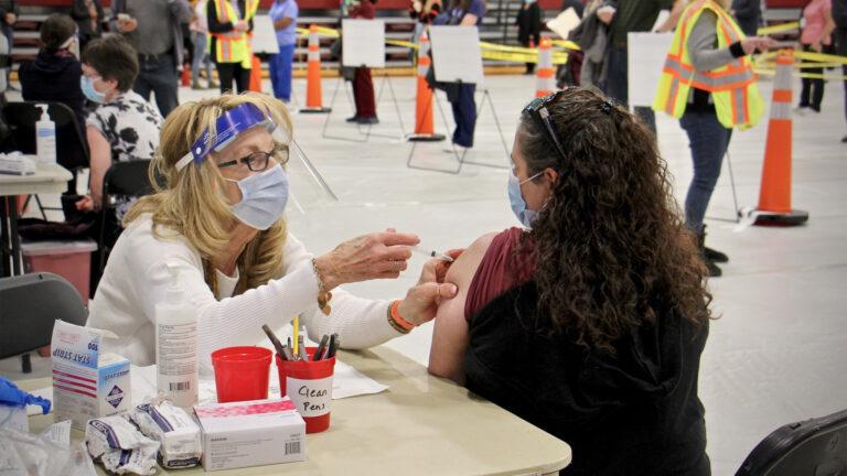 Registered nurse Pat DeHorsey vaccinates physician assistant Dana Steinter