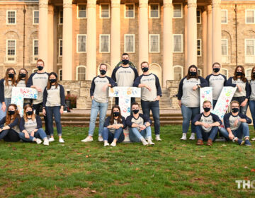 Penn State THON executive leaders sit on campus wearing face masks