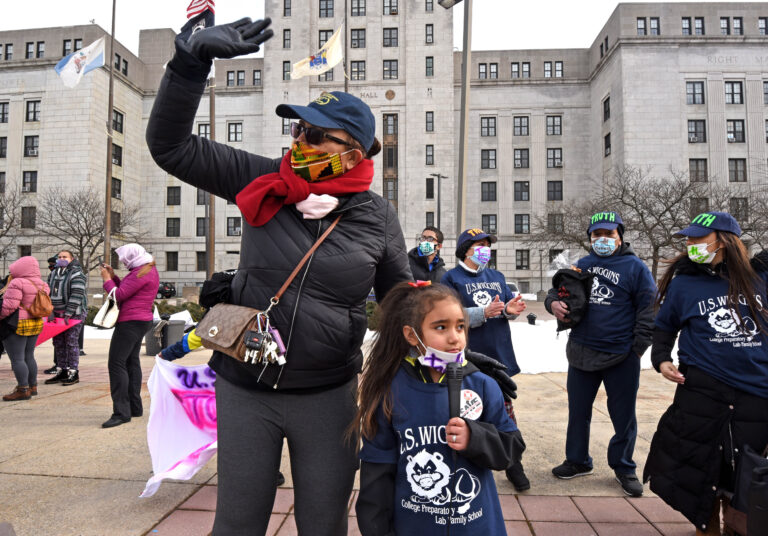 Ednalieze Figueroa, 5, who attends Wiggins School in Camden, protests the closure of her school on Fabruary 6, 2021 with an assist from activist Victoria Pellot.  (April Saul for WHYY)