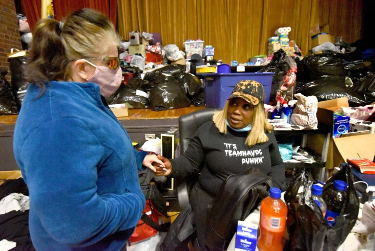 On March 5, 2021, at her warming center in the Yorkship Family School gym, Tawanda Jones, right, tries to convince a patron known as Sarah Ann to allow Jones to help her rent a room at a boarding house. Sarah Ann had told Jones that if there was nowhere else to go that night, she would sleep in Camden's Evergreen Cemetery.  (Photo by April Saul for WHYY)