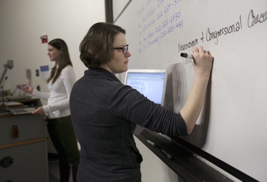 OHSU School of Medicine student Mollie Marr writes in front of a whiteboard. She helps organize a letter-writing campaign for students to share personal stories about the impact of losing a proposed tax waiver for tuition for graduate students, December 1, 2017. Marr is pursuing her M.D. and her Ph.D. in behavioral neuroscience in the OHSU School of Medicine, and losing the tax waiver could mean dropping out of OHSU.