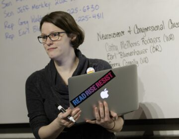 OHSU School of Medicine student Mollie Marr stands in front of a whiteboard holding a laptop. She helps organize a letter-writing campaign for students to share personal stories about the impact of losing a proposed tax waiver for tuition for graduate students, December 1, 2017. Marr is pursuing her M.D. and her Ph.D. in behavioral neuroscience in the OHSU School of Medicine, and losing the tax waiver could mean dropping out of OHSU. (OHSU/Kristyna Wentz-Graff)