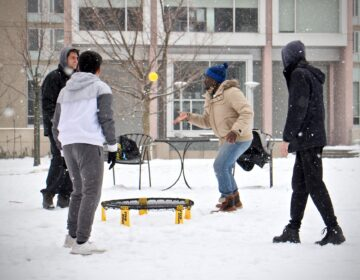 University of Pennsylvania students play a game on a snowy quad. (Emma Lee/WHYY)