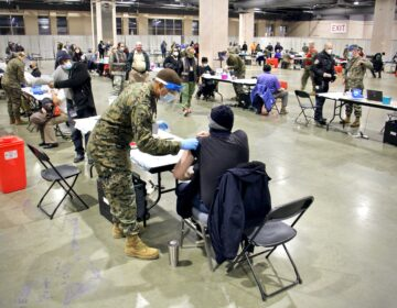 A National Guard member vaccinates someone against COVID-19 at the Pennsylvania Convention Center