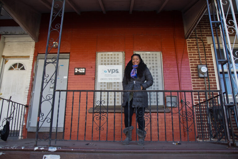 Racqueal Howard on the porch of the property she won in the Philadelphia Housing Authority-Jumpstart lottery in the Mantua section of West Philadelphia. She plans to renovate the home and sell it to a family. (Kimberly Paynter/WHYY)