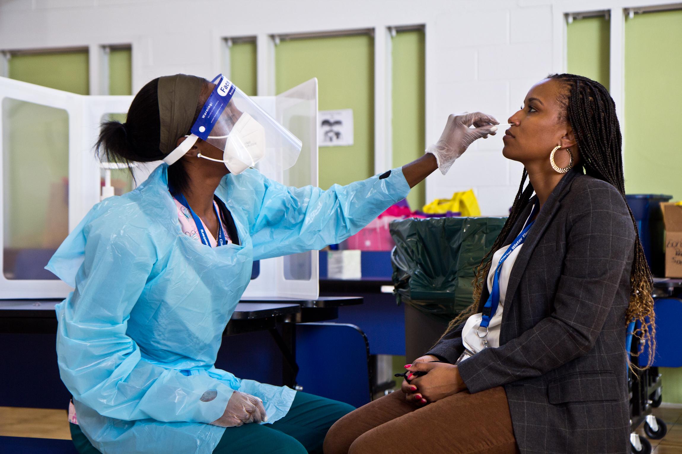 Nurse Paris tests Principal Langston for COVID-19 in the gymnasium