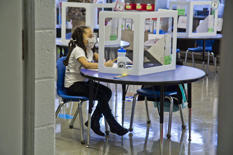A student, wearing a face mask, sits at an isolated desk at school